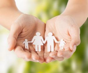 die Hände der Frau mit Papiermannfamilie