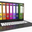 Datei in der Datenbank. Laptop mit farbigen Ringbüchern