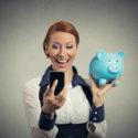glückliche junge Frau, die das Sparschwein betrachtet intelligentes Telefon hält