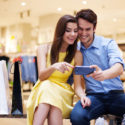 Lächelnde junge Paare, die Handy betrachten