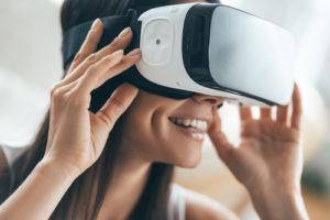 Die Zukunft ist jetzt. Attraktive junge Frau, die ihren VR-Kopfhörer justiert und beim zu Hause sitzen lächelt