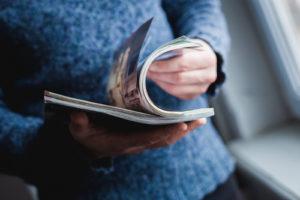 Ein Mann schaut sich eine Zeitschrift an. Drücken Sie die Hände.
