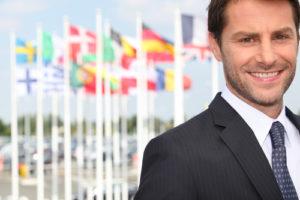 Lächelnde männliche Führungskraft vor verschiedenen Flaggen (Flughafen Bordeaux, Frankreich)