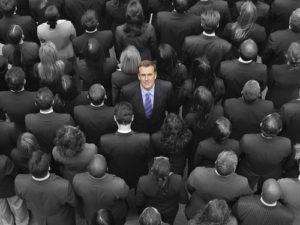 Hohe Winkelsicht eines Geschäftsmannes, der unter grauen Wirtschaftlern steht