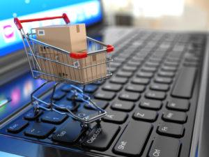 E-Commerce. Einkaufswagen mit Pappschachteln auf Laptop.