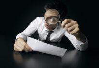 Businessmann schaut sich mit Lupe Vertrag an