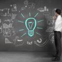 Geschäftsmann, der Zeichnungen auf einer Wand mit einer Glühlampe und verschiedenen Diagrammen betrachtet