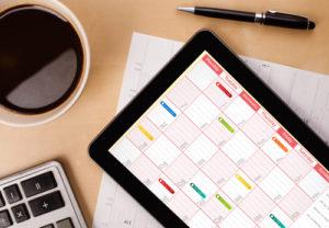 Tablet-PC, der Kalender auf Schirm mit einem Tasse Kaffee an einem Tag zeigt