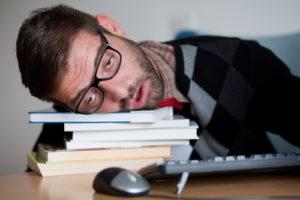 Müder Sonderling, der auf einem Bündel Büchern einschläft