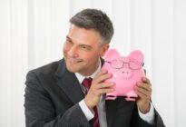 Businessmann hält Sparschwein in den Händen