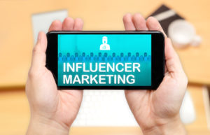 Aufpassen der Hand zwei, Handy mit Influencer-Marketing zu halten