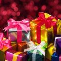 Stapel von kleinen Geschenken auf rotem undeutlichem Lichthintergrund.