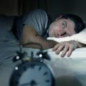 Mann im Bett mit geöffneten Augen leiden an Schlaflosigkeit und Schlafstörung