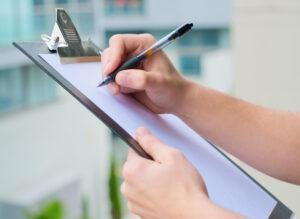 Hände schreiben auf Clipboard