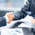 Geschäftsleute, die Hände im Büro rütteln