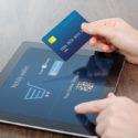 weibliche Hände, die Kreditkarte und eine Tablette im Büro halten