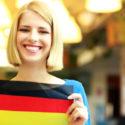 Nettes blondes Mädchen, das Flagge von Deutschland hält