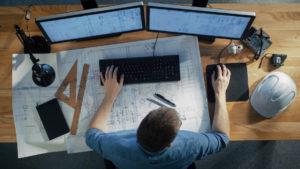 Draufsicht des Architekturingenieurs Working on His Blueprints, Tablet-Computer halten und auch Tischrechner verwenden. Sein Schreibtisch ist voller nützlicher Gegenstände und Abendsonne.
