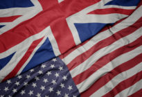 waving colorful flag of united states of america and national flag of great britain. macro