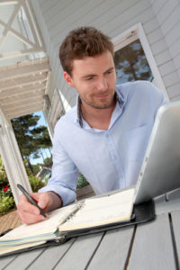 Porträt eines lächelnden Mannes der zuhause an einem Tablet Arbeitet