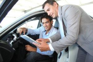 Autoverkäufer mit dem Autokäufer, der auf ein Tablet schaut