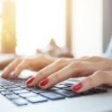 Geerntete Ansicht des Studentenmädchens das zufällige Hemd tragend, das für Prüfungen bei der Anwendung des Computers sich vorbereitet. Junger weiblicher Freiberufler, der im gemütlichen Café unter Verwendung des drahtlosen Internets arbeitet. Vorgewählter Fokus auf Schreibenhänden
