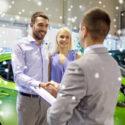 glückliches Paar mit Autohändler in Auto Show