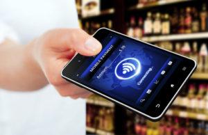 Hand, die Handy mit mobilem Zahlungsschirm hält