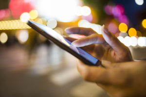 Frau, die ihren Handy in der Straße, Nachtlicht Environm verwendet