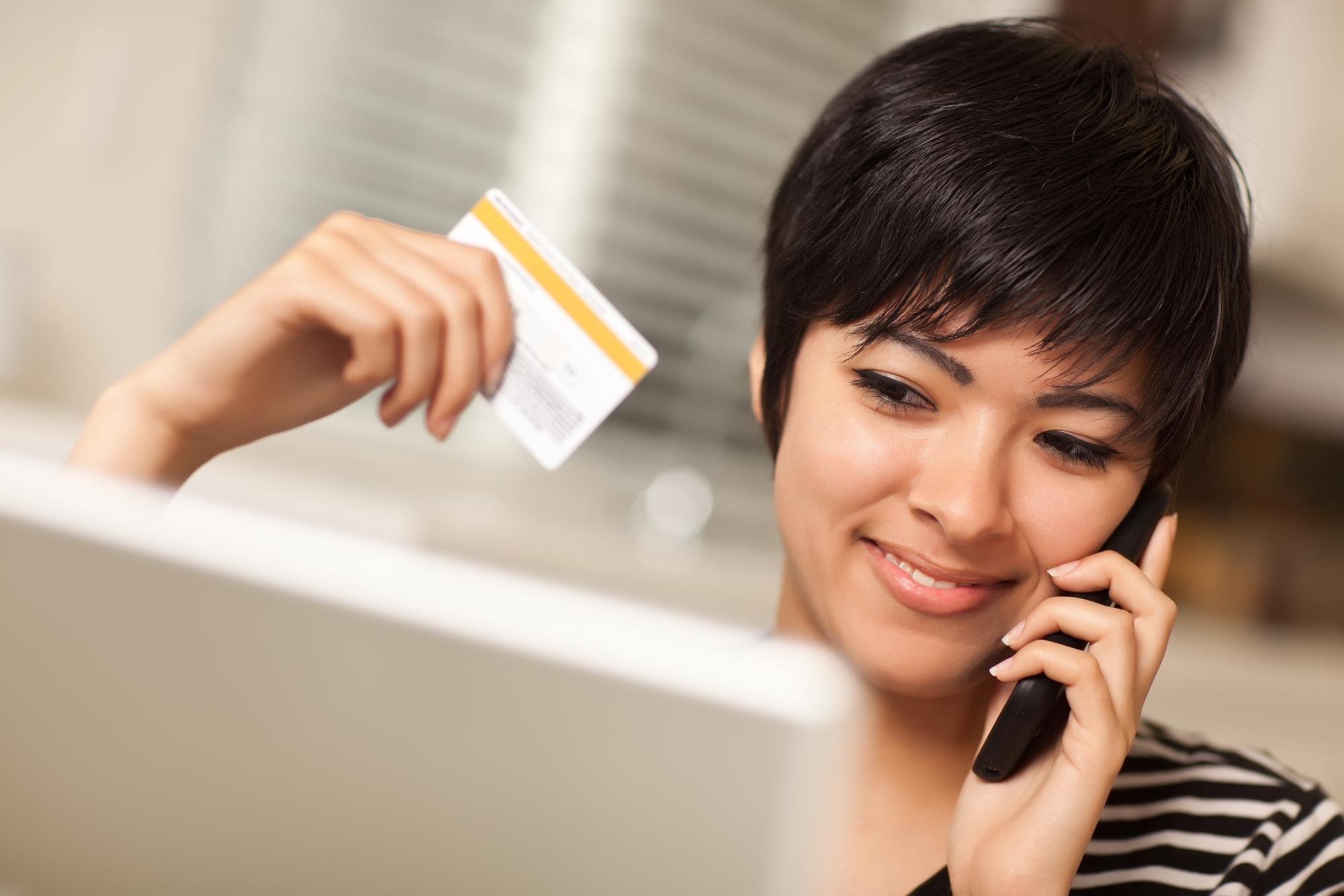 Recht junge multiethnische Frau, die Telefon und Kreditkarte unter Verwendung des Laptops hält.
