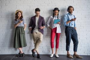 Vier verschiedene Personen stehen vor einer Wand und benutzen ihre Handys