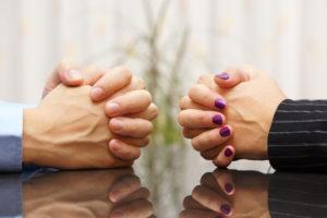 Mann und Frau sitzt an einem Schreibtisch mit gefalteten Händen. Eheproblem