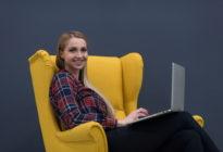 Startup-Unternehmen, Frau arbeitet am Laptop und sitzt auf gelb