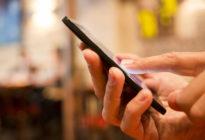 Mann, der einen Handy im Restaurant, Café, Bar verwendet