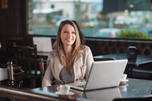 Schöne Frau im Café mit einem Laptop