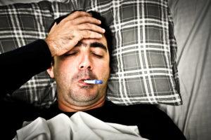 Drastisches Bild eines kranken Mannes im Bett mit Fieber