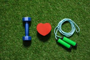 Draufsicht der bunten Hantel mit Herzsymbol und Springseil auf dem Gras