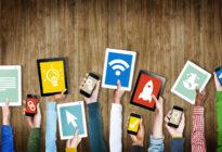 Gruppe Hände, die digitale Geräte mit Symbolen halten
