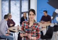 Porträt der jungen Geschäftsfrau im Büro mit Team im Hintergrund
