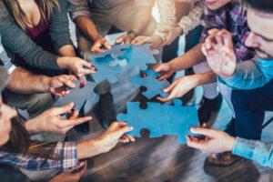 Wirtschaftler, die sich Puzzlespielstücken im Büro, Abschluss oben anschließen.