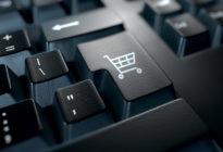 Nahaufnahme einer Tastatur mit der Eingabetaste durch ein Warenkorb-Symbol ersetzt. E-Commerce-Konzept