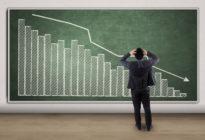 Stressiger Geschäftsmann, der ein sinkendes Diagramm betrachtet