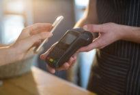 Frau, die Rechnung durch Smartphone unter Verwendung NFC-Technologie zahlt