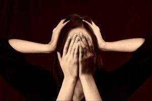 Stress: Gesicht mit Händen davor