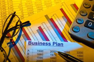 Businessplan mit Statistik, Brille und Taschenrechner