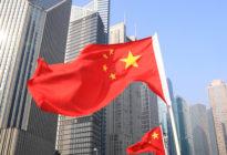 Skyline von verscheidenen Wolkenkratzern, davor wehen chinesische Flaggen.