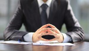 Geschäftsmann mit Dokumenten auf dem Schreibtisch