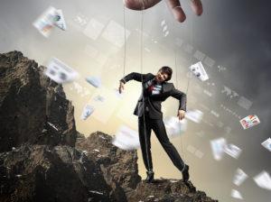 Geschäftsmann als Marionette stehend auf einem Berg