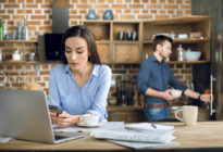 Frau, die Freelancer ist, sitzt mit Kaffee, Laptop un Smartphone am Küchentisch, im Hintergrund befindet sich ein Mann