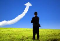 Geschäftsmann auf einer Wiese, der einem Pfeil aus Wolken, der nach oben führt, zuschaut